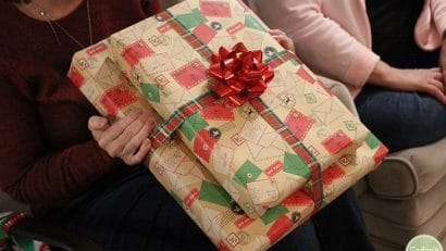 Hands holding a wrapped Christmas present.