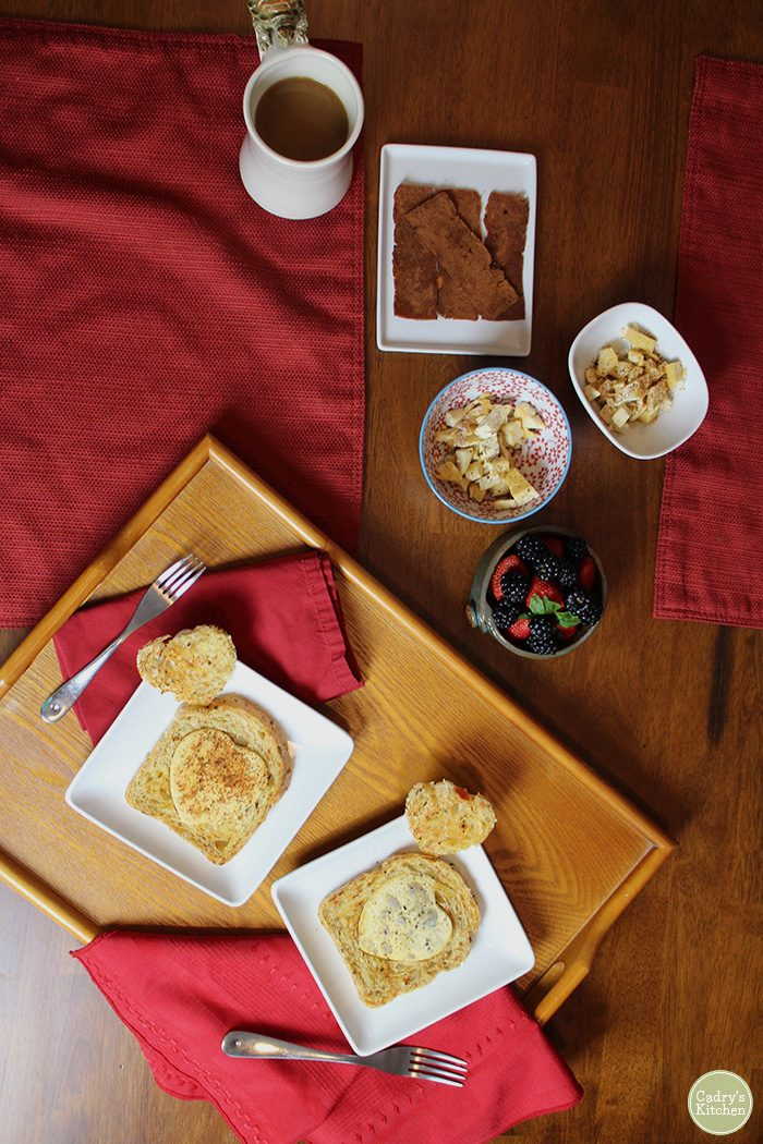 Valentine's day breakfast. Tray with vegan egg in a hole, seitan bacon, and coffee on table.