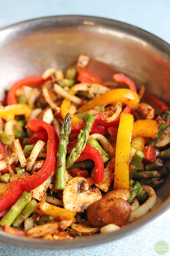 Asparagus, onions, peppers, and mushrooms in mixing bowl.