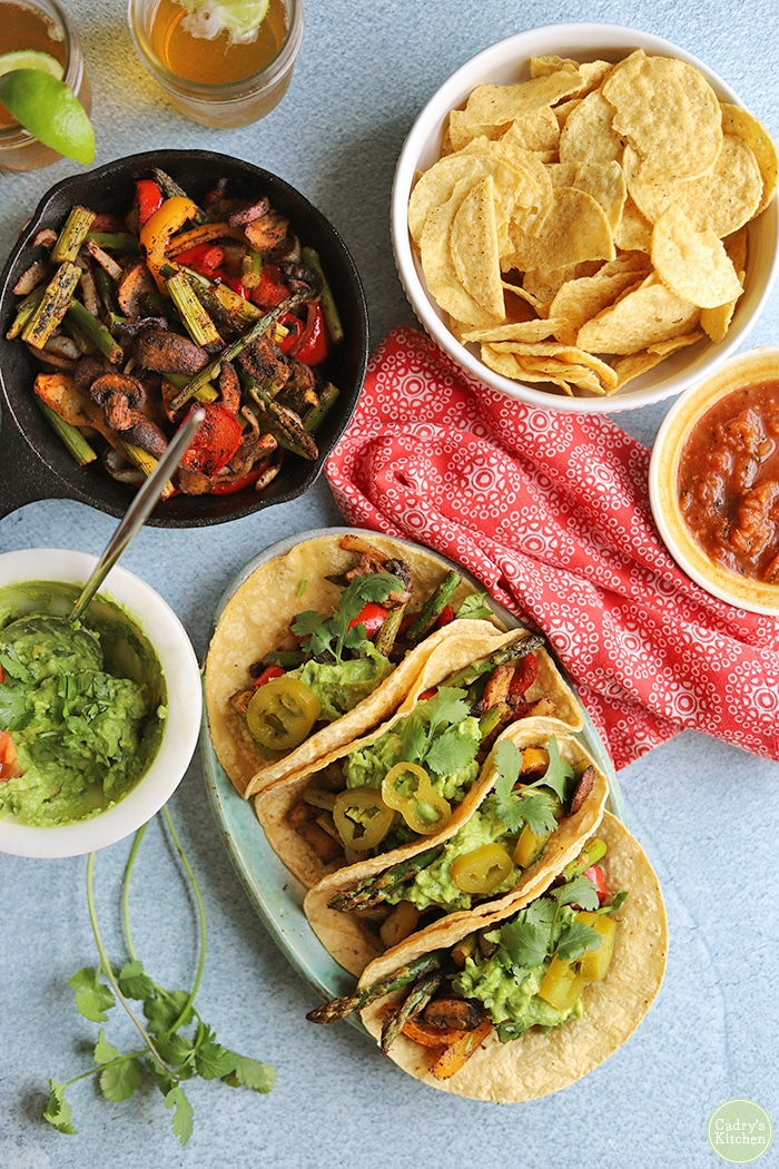 Overhead grilled vegetable fajitas with guacamole, chips, and salsa.