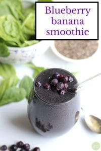 Text: Blueberry banana smoothie. Smoothie in glass with blueberries on top.