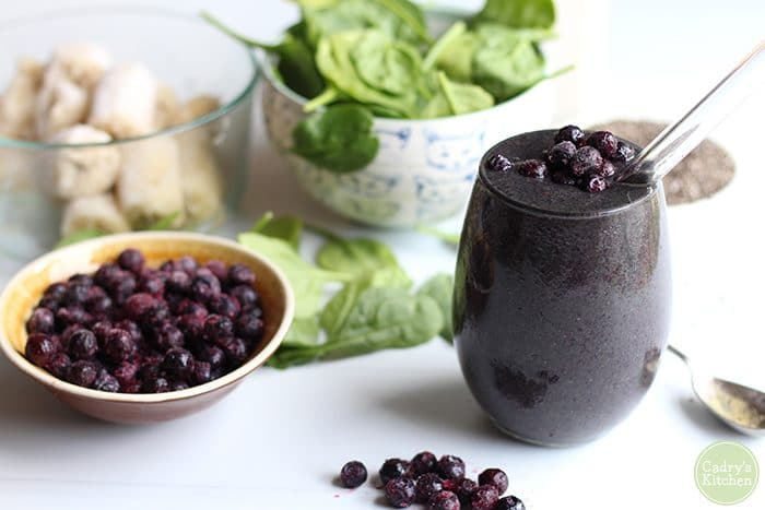 Vegan blueberry banana smoothie in glass. Spinach, frozen bananas, and blueberries in background.