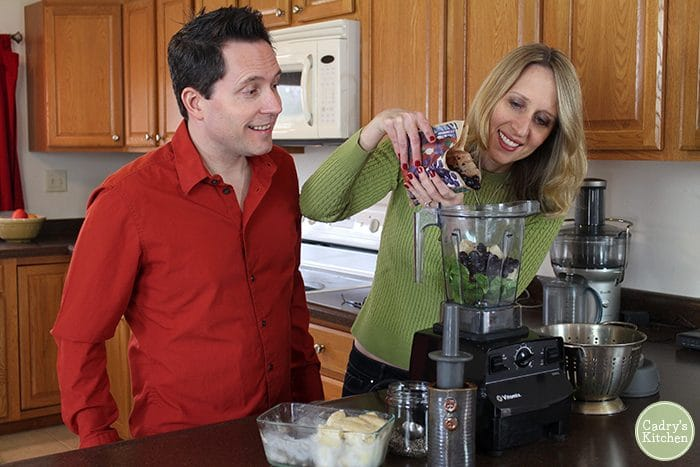 Cadry pouring blueberries into Vitamix blender while David watches.