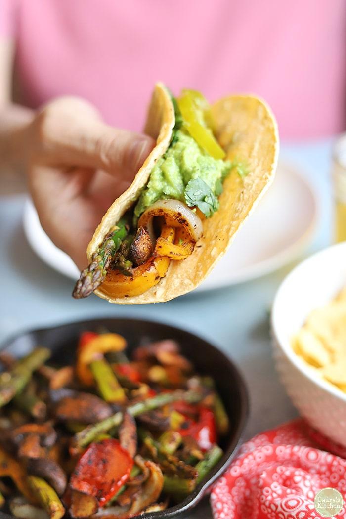 Hand holding veggie fajitas in corn tortilla.
