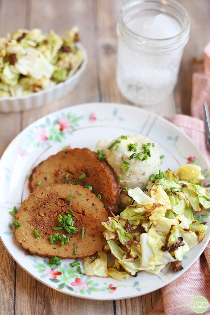 Vegan dinner on plate with seitan slices, mashed potatoes, and crispy cabbage side dish.