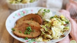 Roasted cabbage on plate with mashed potatoes and sliced Field Roast celebration roast.