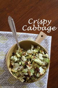Overhead roasted cabbage in a bowl with spoon + text.
