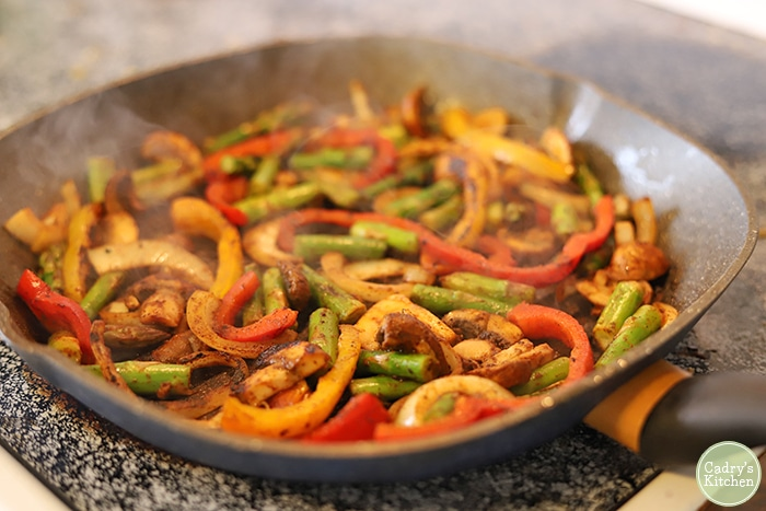 Asparagus, mushrooms, peppers, and onions on indoor grill pan.