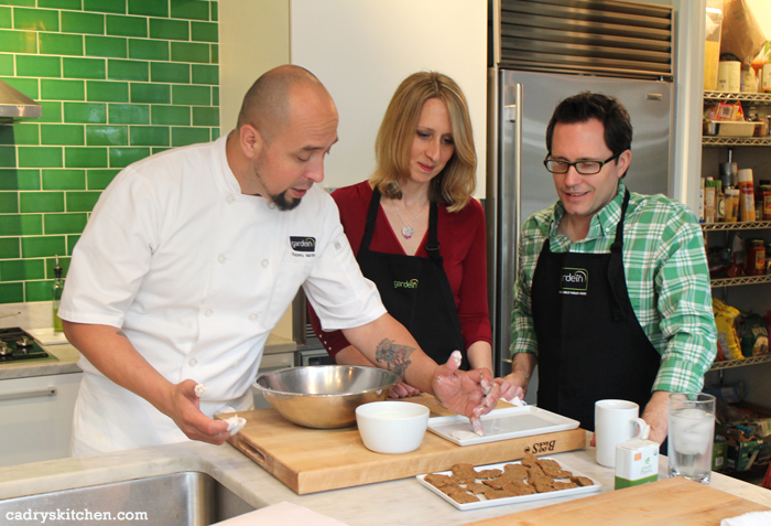 Chef Roberto Martin shows Cadry Nelson and David Busch how to bread chick'n fried steak in the Gardein tasting kitchen.