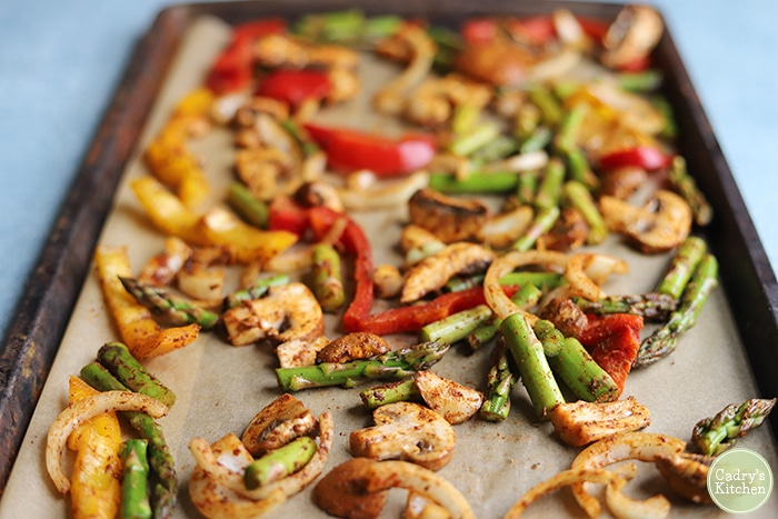 Mushrooms, asparagus, onions, and bell pepper on baking sheet.