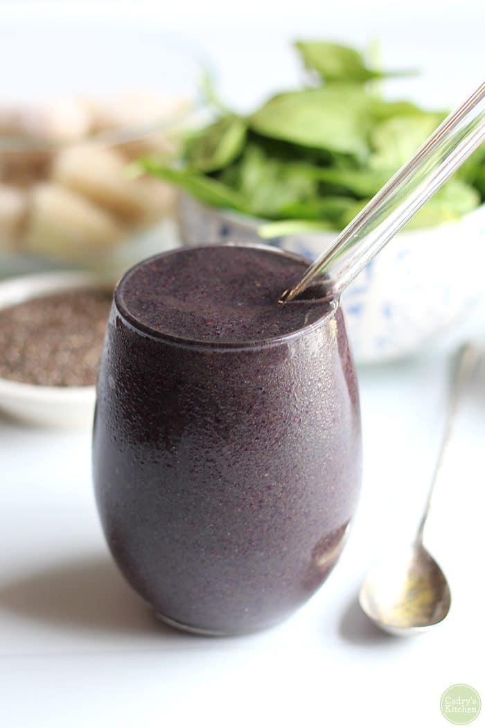 Vegan blueberry banana smoothie in a glass with spinach and chia seeds in background.