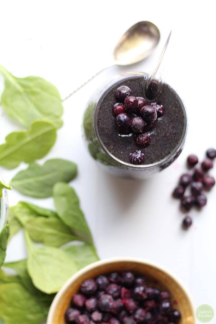 Overhead vegan blueberry banana smoothie with spinach and frozen blueberries.