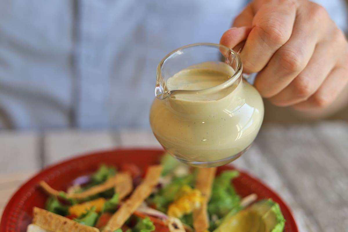 Small pitcher of dressing by salad.