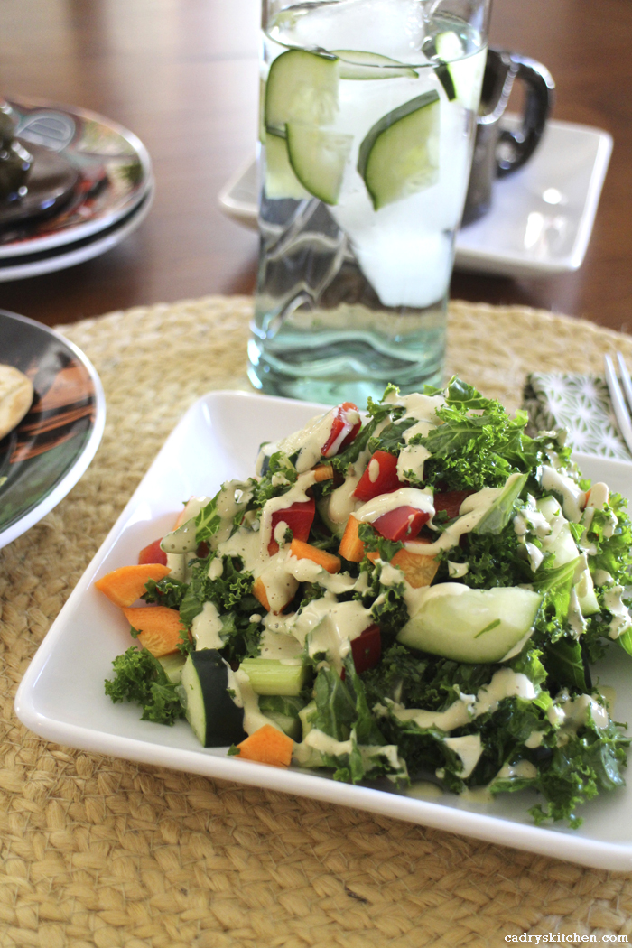 Creamy cashew salad dressing on kale salad with cucumber water.