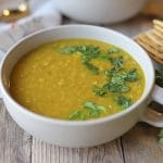 Curried red lentil soup in bowl with cilantro.