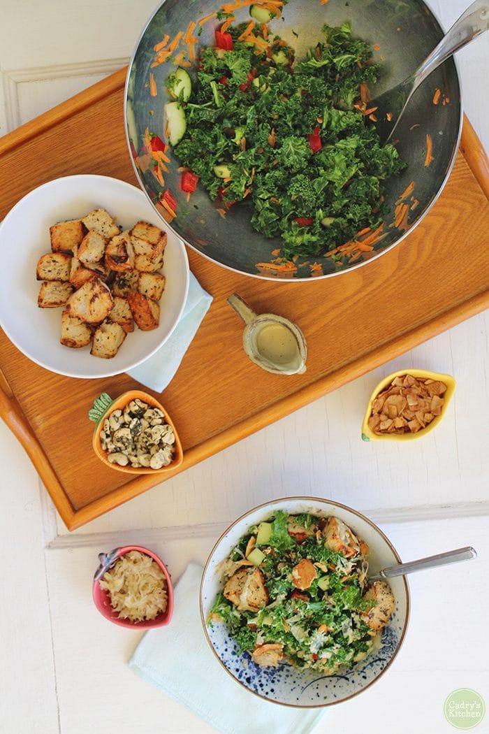 Overhead kale salad in bowls, croutons, marinated cashews, and creamy cashew salad dressing.