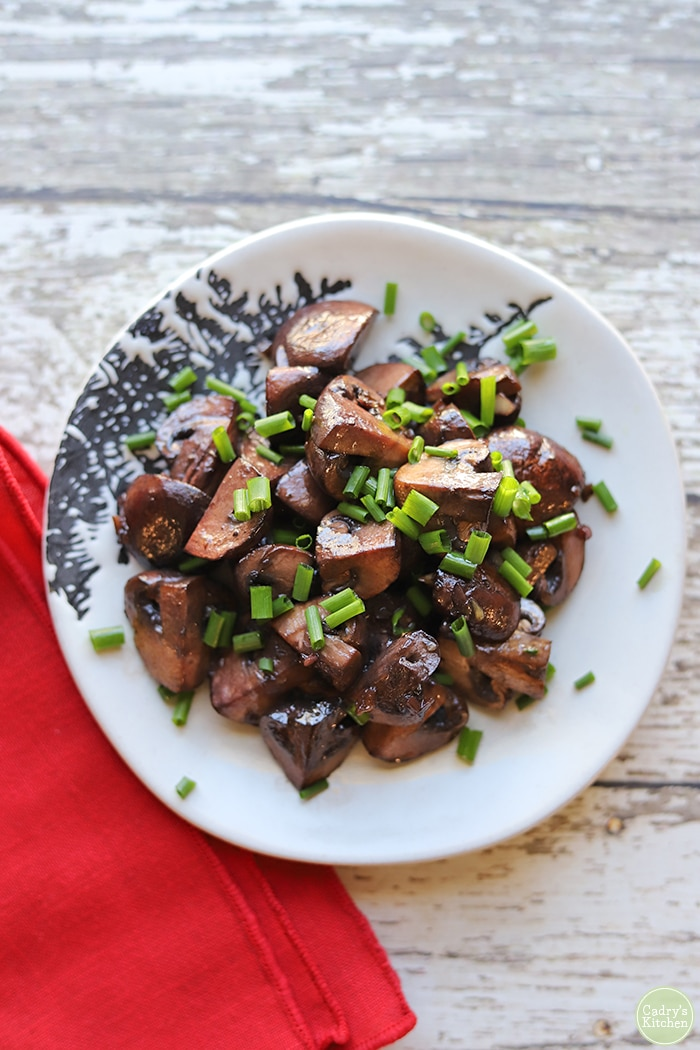 Overhead red wine mushrooms on white plate, topped with chopped chives.