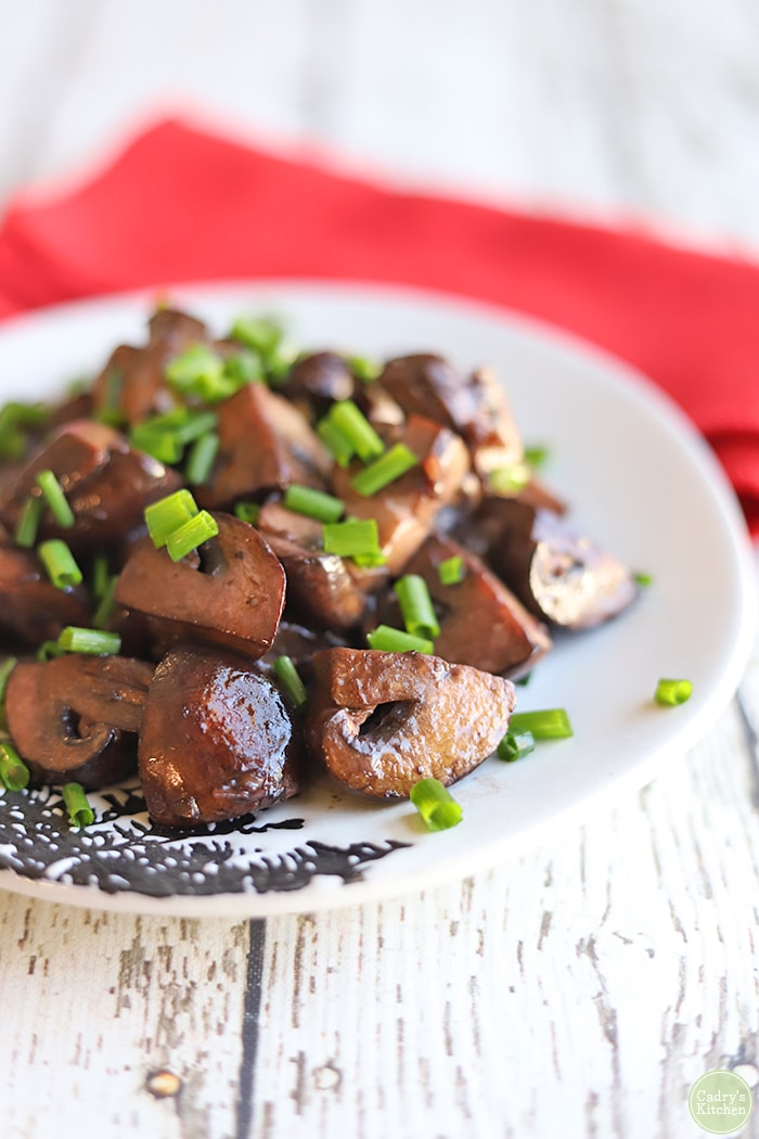 Red wine mushrooms on plate with chives.