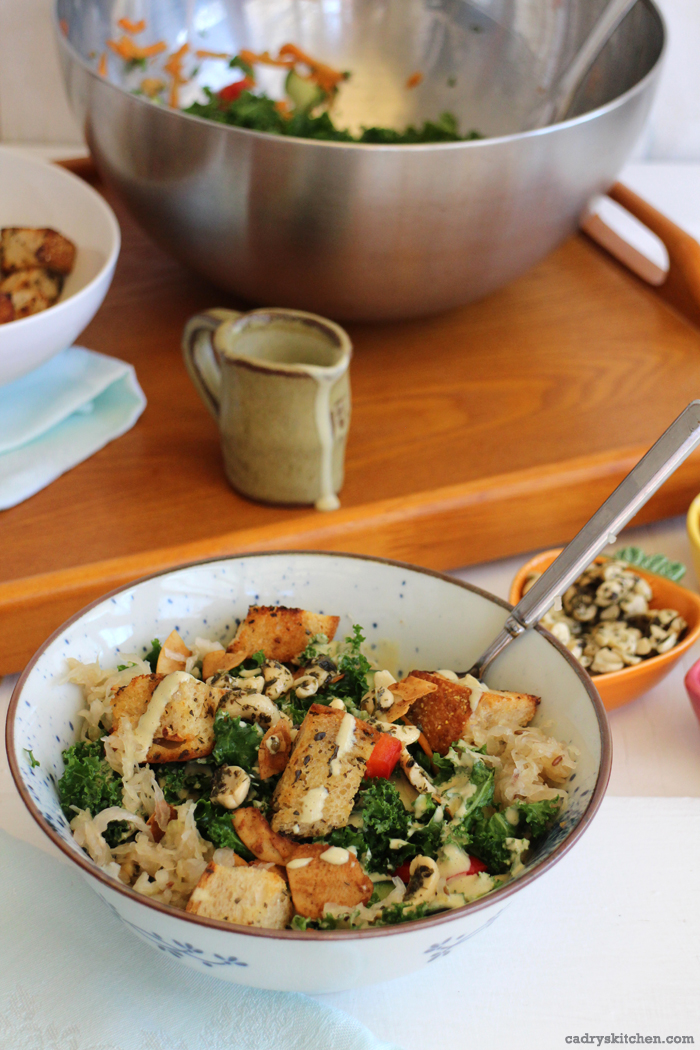 Creamy cashew salad dressing on kale salad with bowl and pitcher in background.
