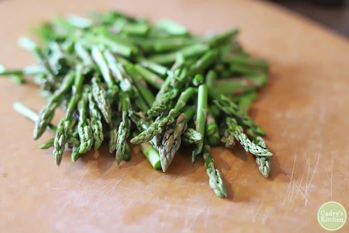 Asparagus pieces on cutting board.