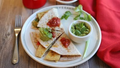 Quesadilla on plate with guacamole and salsa.