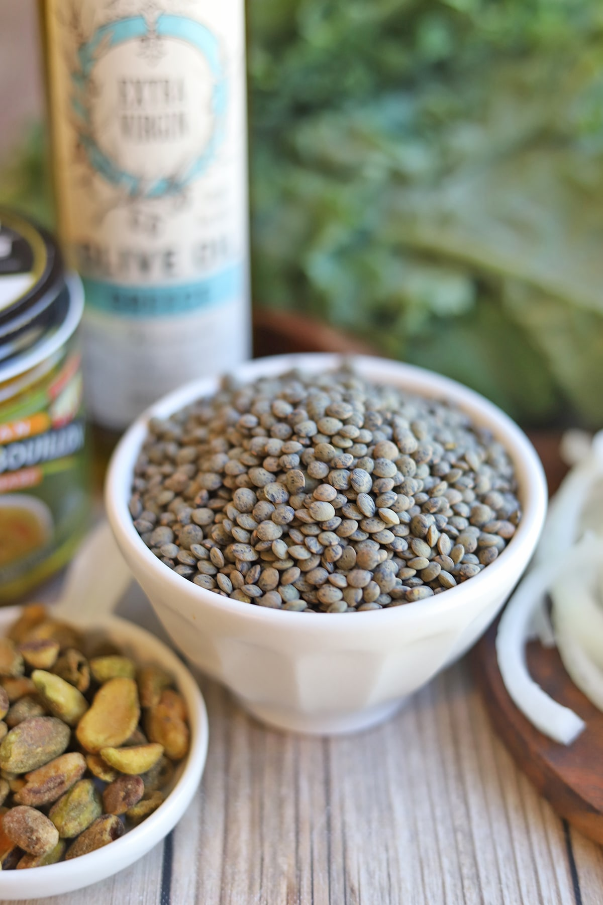 Dried French lentils in white bowl by olive oil and pistachios.