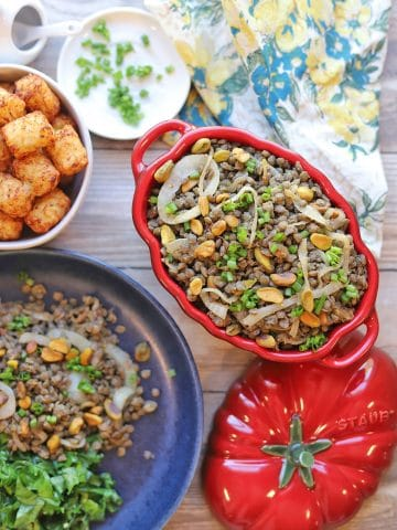 Overhead red serving dish with Puy lentils, tater tots, and kale.