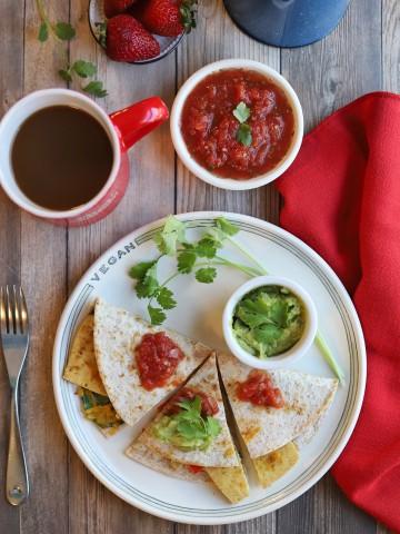 Overhead breakfast quesadilla with salsa, guacamole, and cilantro.