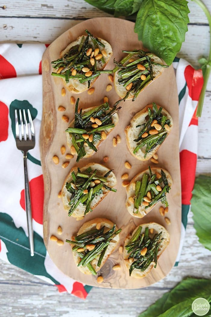 Overhead asparagus appetizers with toasted pine nuts on board.