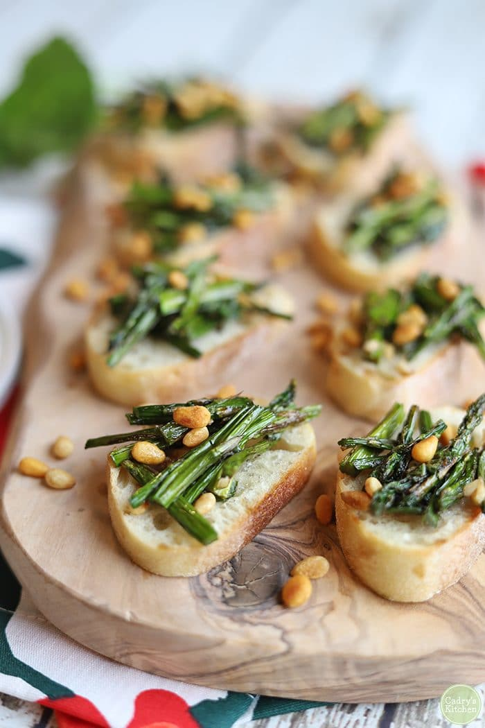Roasted asparagus appetizer with pine nuts on board.