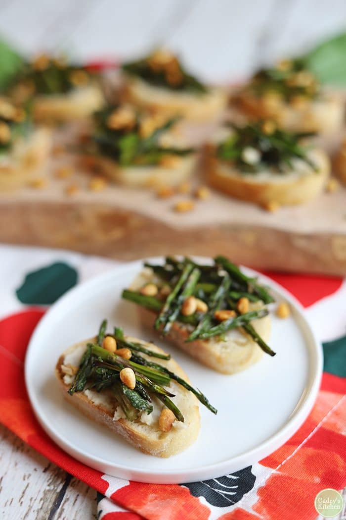 Roasted asparagus with pine nuts on toasted baguette on small plate.