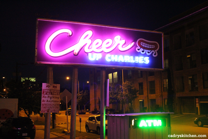 Cheer Up Charlies sign lit up at night.