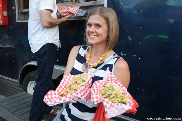 Kristy by Arlo's food truck, holding two baskets of tacos.