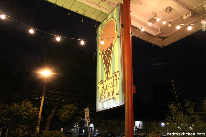 Sweet Ritual sign and hanging lights at night.