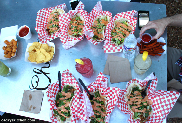 Overhead table full of baskets of tacos, chips, and salsa.