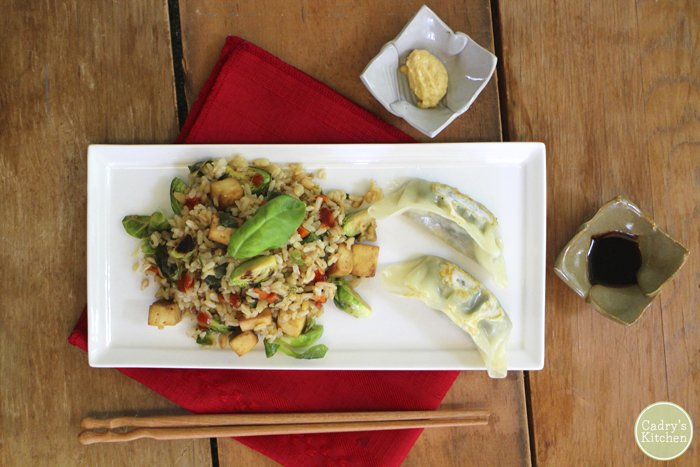 Brussels sprouts fried rice on plate with potstickers and dipping sauces.