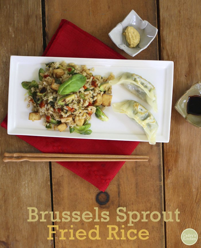 Text overlay: Brussels sprouts fried rice. Rice on plate with potstickers, chopsticks, and dipping sauces.