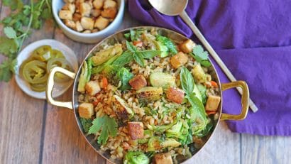 Overhead fried rice in metal dish, jalapeno peppers, and cubed tofu.