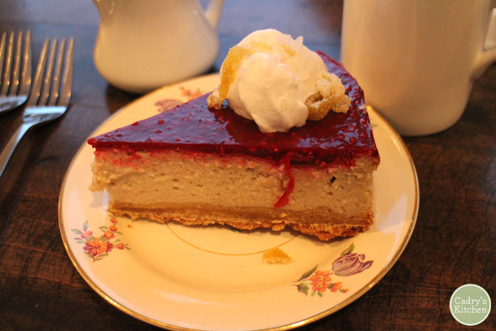 A slice of raspberry cheesecake on a flowered plate.