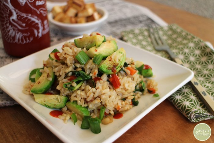 Brussels sprouts fried rice on plate with sriracha and fried tofu.