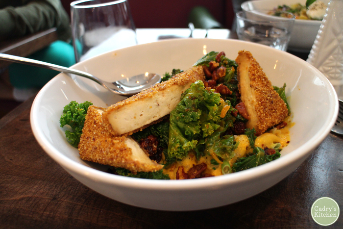 A bowl of mac and shews with cornmeal crusted tofu & curly kale.