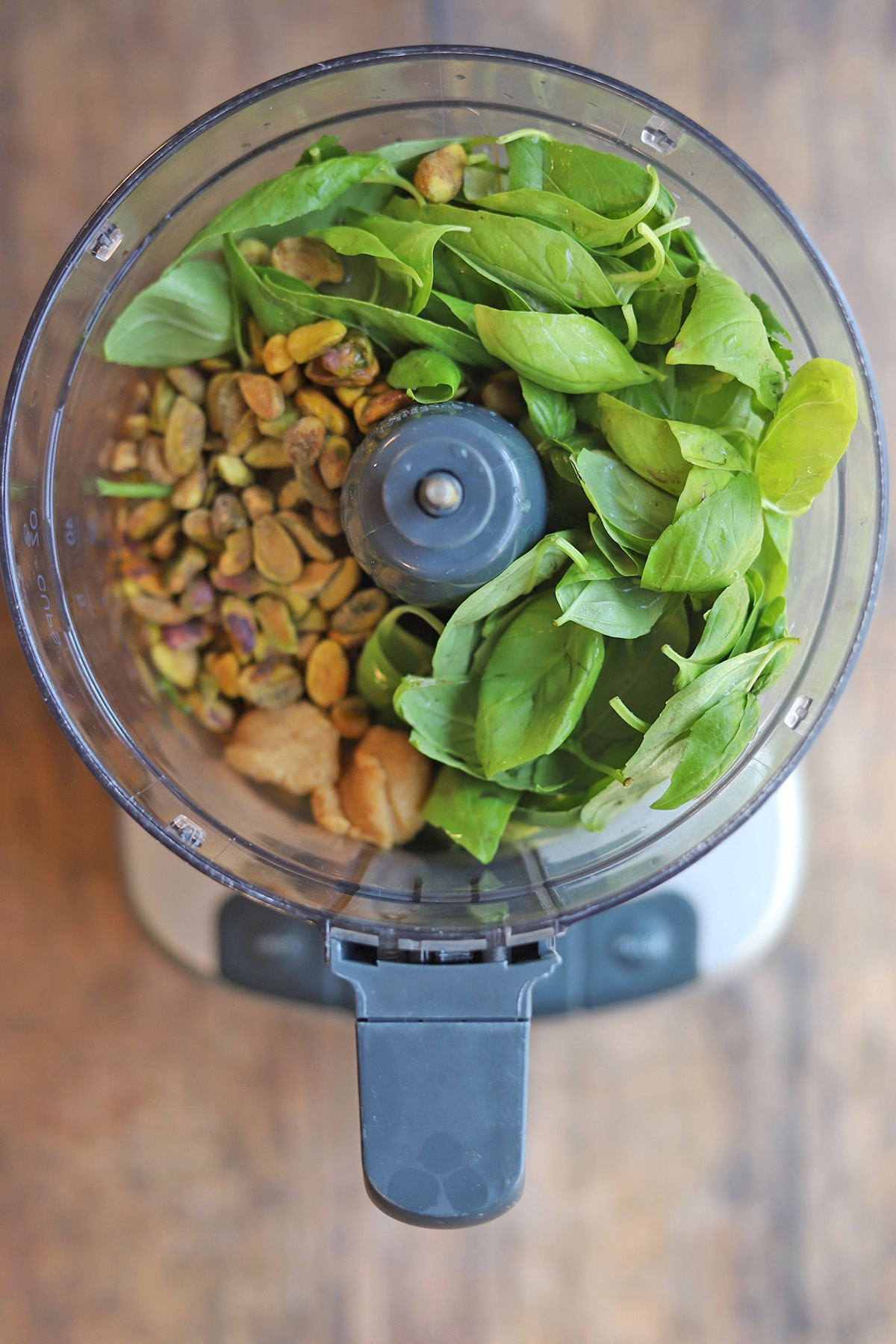 Overhead food processor with basil, pistachios, garlic, and miso paste.