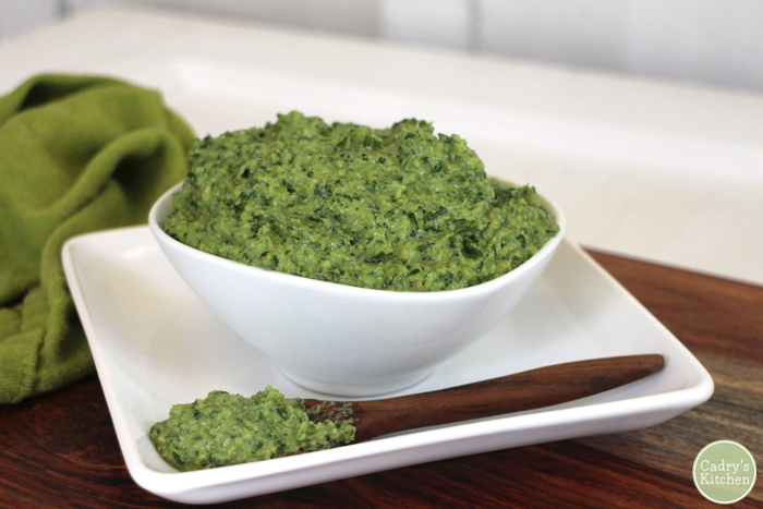 Small bowl of cilantro basil pesto with wooden spoon.