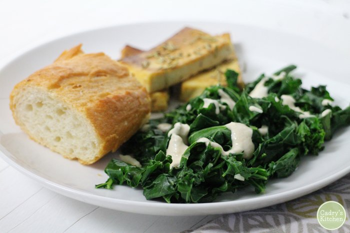 Kale with tahini sauce, baked tofu, and bread on plate.