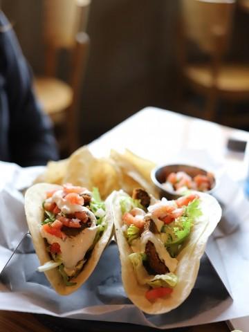 Fried avocado tacos on taco stand.