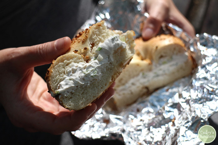 Hand holding bagel stuffed with non-dairy cream cheese.