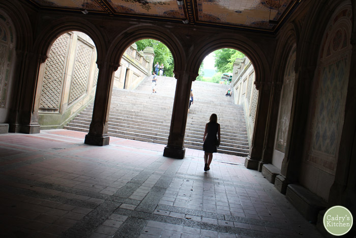 Silhouette of Cadry walking through arches in Central Park structure.