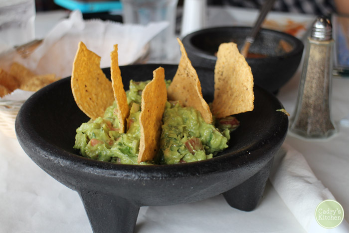 Guacamole in molcajete with tortilla chips.