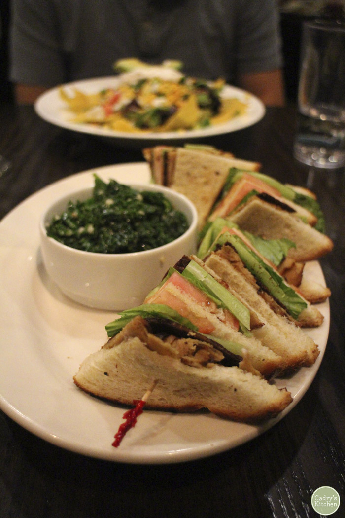 Smoked tofu club sandwich and greens on plate at Chicago Diner.