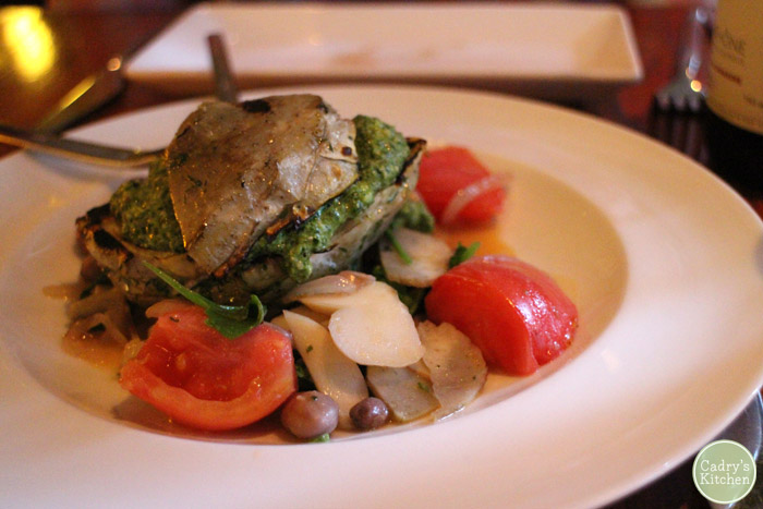 Grilled artichoke heart with pesto, beans, and tomato in shallow bowl.